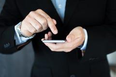 工作在他的手机的一位年轻执行委员 免版税库存图片