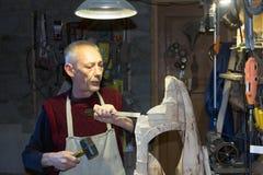 工作在他的木制品车间的木匠 免版税库存照片