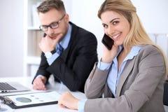 工作在会议上的两个成功的商务伙伴在办公室 在金发碧眼的女人的焦点,当谈话由电话时 免版税库存照片