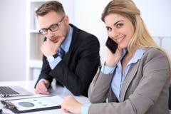 工作在会议上的两个成功的商务伙伴在办公室 在金发碧眼的女人的焦点,当谈话由电话时 免版税图库摄影