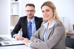 工作在会议上的两个成功的商务伙伴在办公室 在金发碧眼的女人的焦点 图库摄影