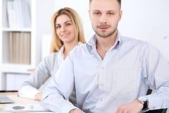 工作在会议上的两个成功的商务伙伴在办公室 背景美丽的重点人三晚礼服妇女 免版税图库摄影