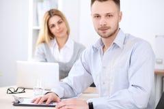 工作在会议上的两个成功的商务伙伴在办公室 背景美丽的重点人三晚礼服妇女 免版税库存图片