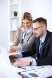 工作在会议上的两个成功的商务伙伴在办公室 免版税库存图片