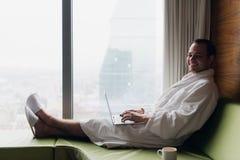 工作在便携式计算机佩带的白色浴袍的年轻微笑的商人坐在与咖啡的窗口附近 免版税库存图片