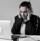 工作在便携式计算机在遭受强烈的头疼和偏头痛的重音的办公桌的妇女 免版税库存照片