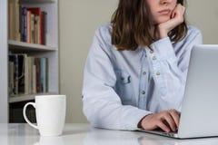 工作在便携式计算机的乏味人 免版税库存照片