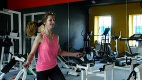 工作在健身房的健身的年轻运动妇女与跳绳和健康惯例 股票视频