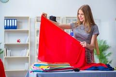 工作在关于新的礼服的车间的少妇裁缝 图库摄影