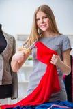 工作在关于新的礼服的车间的少妇裁缝 库存图片