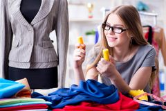 工作在关于新的礼服的车间的少妇裁缝 库存照片