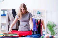工作在关于新的礼服的车间的少妇裁缝 免版税图库摄影