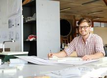 工作在制图桌上的年轻建筑师在建筑师演播室 免版税库存图片