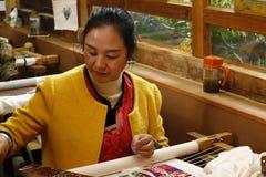 工作在刺绣的妇女在白沙,丽江,云南,中国村庄  免版税库存照片