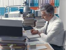 工作在办公室和堆的商人文书工作 免版税库存图片