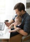 工作在办公室和照顾小儿子的年轻父亲 免版税库存图片