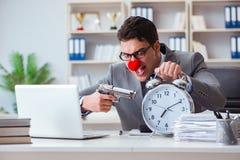 工作在办公室恼怒沮丧的小丑商人与a 免版税库存图片