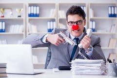 工作在办公室恼怒沮丧的小丑商人与a 图库摄影