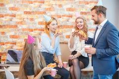 工作在办公室的一个小组男人和妇女,吃在一种欢乐心情的薄饼 免版税库存图片
