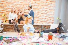 工作在办公室的一个小组男人和妇女,吃在一种欢乐心情的薄饼 一个女孩的特写镜头用薄饼投入了她 图库摄影