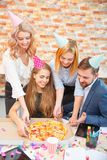 工作在办公室的一个小组男人和妇女,吃在一种欢乐心情的薄饼 库存照片