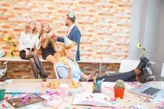 工作在办公室的一个小组男人和妇女,吃在一种欢乐心情的薄饼 一个女孩的特写镜头用薄饼投入了她 库存照片