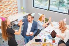 工作在办公室的一个小组男人和妇女,吃在一种欢乐心情的薄饼 免版税库存照片