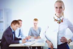 工作在办公室的一个少妇的画象站立与文件夹 一个少妇的纵向 2 business woman 免版税库存照片