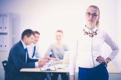 工作在办公室的一个少妇的画象站立与文件夹 一个少妇的纵向 2 business woman 免版税库存图片