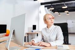 工作在办公室的一名严肃的成熟女实业家的画象 免版税库存图片