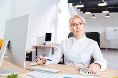 工作在办公室的一名微笑的女实业家的画象 免版税库存图片