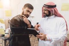 工作在办公室的两个阿拉伯人 工友采取在玻璃委员会前面的笔记 库存照片