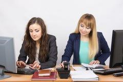 工作在办公室的两个年轻女商人在工作场所在同一张桌上 库存照片