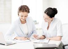 工作在办公室的两名微笑的女实业家 免版税图库摄影