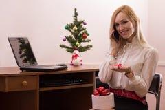 工作在办公室的可爱的妇女在圣诞节 免版税库存图片