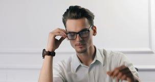 工作在办公室的可爱的聪明的年轻商人律师医生经理程序员办公室工作者 修理他的玻璃和 股票视频