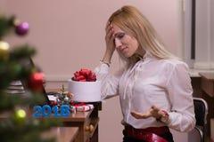 工作在办公室的哀伤的妇女在圣诞节 库存照片
