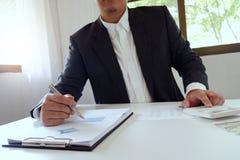 工作在办公室的商人使用有文件的计算器在书桌上 免版税库存图片