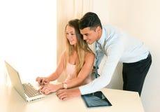 年轻工作在办公室的女商人和英俊的人 库存照片