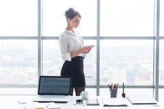 工作在办公室的女实业家,站立在她的与膝上型计算机的工作表附近和固定式,浏览信息读书 免版税库存照片