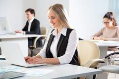 工作在办公室的女实业家 免版税库存照片