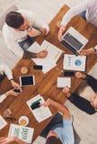 工作在办公室的小组繁忙的商人,顶视图 图库摄影