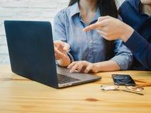 工作在办公室的年轻人和妇女 指向labtop的女商人 Coworking,配合,商务伙伴概念 库存图片