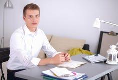 工作在办公室的年轻商人,坐在书桌附近 免版税库存图片