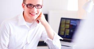 工作在办公室的年轻商人,坐在书桌附近 免版税图库摄影