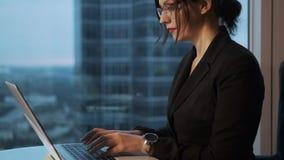 工作在办公室的年轻女人坐由大窗口 研究膝上型计算机的女商人的画象 股票视频
