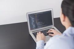 工作在办公室的年轻女商人程序员 编码和编程在屏幕膝上型计算机的妇女手,在编程的概念 免版税库存图片