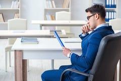 工作在办公室的年轻英俊的商人雇员在书桌 免版税库存图片