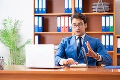 工作在办公室的年轻雇员 免版税库存照片
