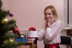 工作在办公室的微笑的妇女在圣诞节 免版税库存照片